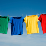 Four brightly colored tee shirts hanging on clothesline