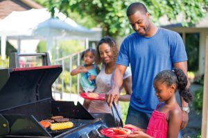 Family cooking hot dogs hamburger and corn on gas grill