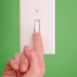 Hand with finger extended to touch bottom of light switch
