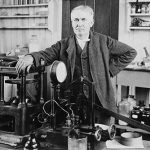 Thomas Edison standing next to equipment on work bench