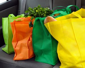 Close up of four reusable grocery bags on back seat of car