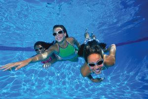 Three teenage girls swimming underwater