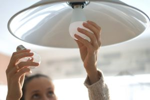 Woman changing light bulb in overhead light to energy efficient bulb