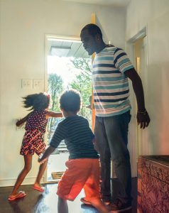 Father opening door to house leaving with son and daughter