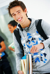 Male teenager holding books in school hallway smiling at camera