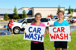 Two teenage girls holding car wash signs while cars are being washed in background