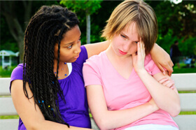 Two female teens sitting on park bench with one wrapping arm around the other in consolation