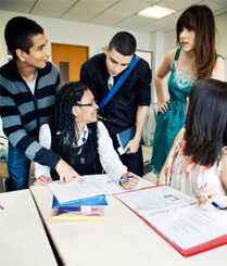 Group of students helping other students sitting at table doing work