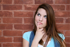 Female student standing against brick wall looking up with index finger on mouth thinking