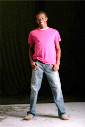 Male teenager smiling at camera standing against black background
