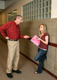 Male teacher conversing with female student standing in school hallway