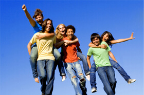 Group of teens outside smiling at camera