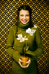 Smiling woman holding a white orchid planter looking at camera