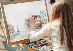 Woman with paints and canvas painting buildings