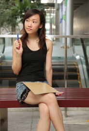 Young Asian woman sitting on bench in mall