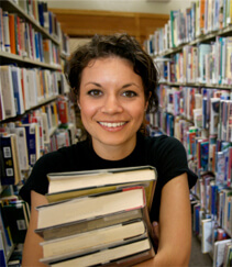 Young woman holding books while walking through library