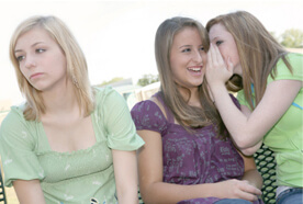 Two female teenagers whispering to each other while another female teenager looks away upset