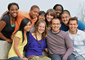Diverse group of people smiling at camera all huddled together for photo