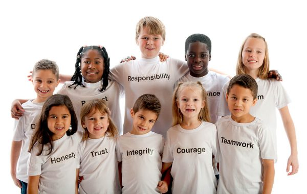Group of young children standing close together wearing white t-shirts with character trait printed in black on shirt