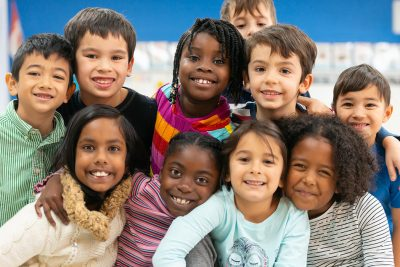 Group of diversified young children smiling at camera