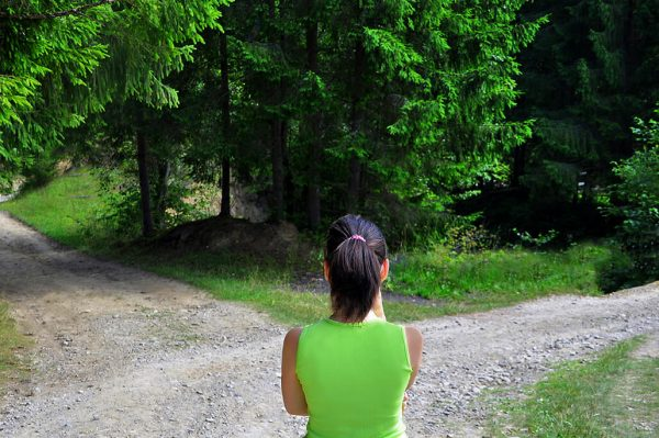 Girl in woods on dirt path deciding which path to take at crossroad