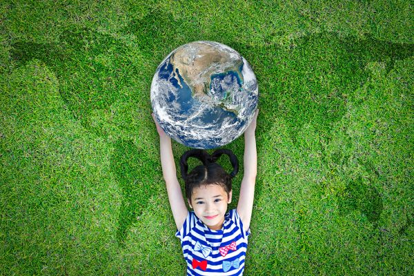 Young girl laying on grass holding globe over head with continents imprinted in grass