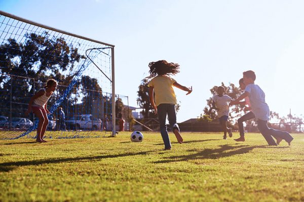 Children playing soccer on field on sunny day